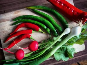 red and green chilis and red bell pepper on brown chopping board