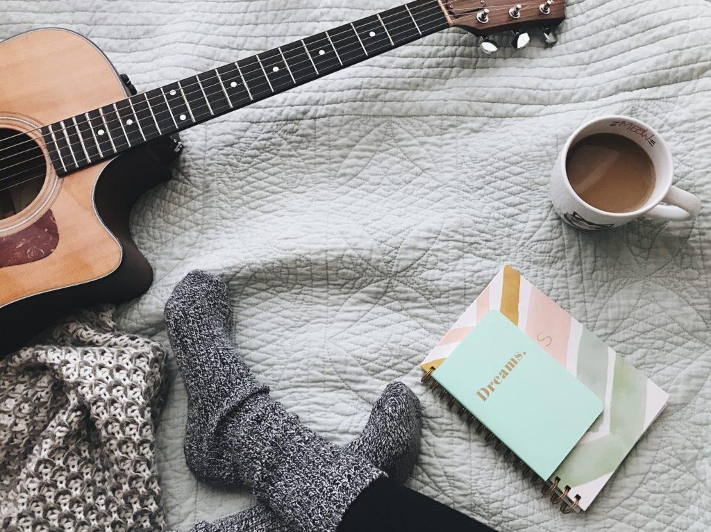 person wearing gray socks near acoustic guitar